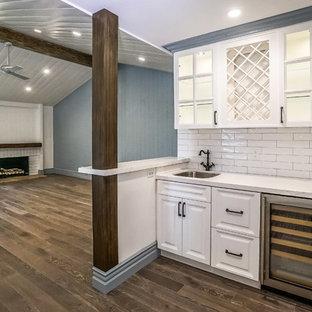 ロサンゼルスの中サイズのミッドセンチュリースタイルのおしゃれなファミリールーム (ホームバー、青い壁、濃色無垢フローリング、標準型暖炉、レンガの暖炉まわり、テレビなし、茶色い床) の写真