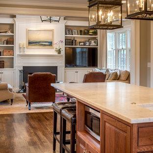 Idee per un soggiorno classico aperto e di medie dimensioni con pareti beige, camino classico, cornice del camino in legno, parete attrezzata e pavimento in mattoni
