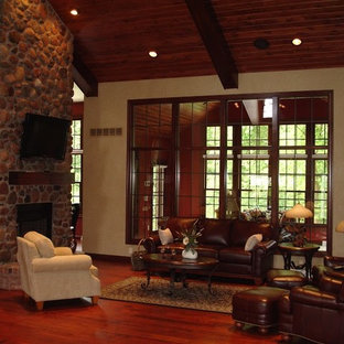 Large mountain style open concept dark wood floor family room photo in Other with beige walls, a two-sided fireplace, a stone fireplace and a wall-mounted tv