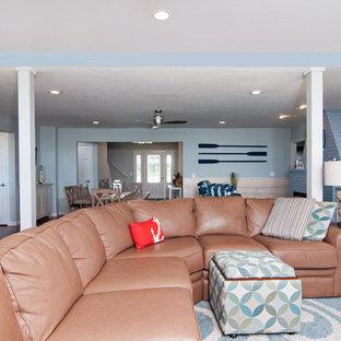 シカゴの大きいビーチスタイルのおしゃれなファミリールーム (青い壁、無垢フローリング、標準型暖炉、レンガの暖炉まわり、据え置き型テレビ、茶色い床) の写真