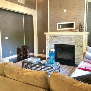 Imagen de sala de estar abierta, tradicional renovada, de tamaño medio, sin televisor, con paredes grises, suelo de madera oscura, chimenea tradicional, marco de chimenea de baldosas y/o azulejos y suelo marrón