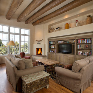 Mid-sized mediterranean open concept family room in Albuquerque with beige walls, medium hardwood floors, a corner fireplace, a freestanding tv, a library and a plaster fireplace surround.