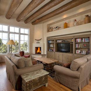 Ispirazione per un soggiorno mediterraneo aperto e di medie dimensioni con pareti beige, pavimento in legno massello medio, camino ad angolo, TV autoportante, libreria e cornice del camino in intonaco