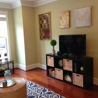 Exemple d'une salle de séjour chic de taille moyenne et fermée avec un mur vert, un sol en bois brun et un téléviseur indépendant.