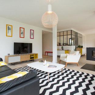 Cette image montre une grande salle de séjour design ouverte avec un mur blanc, un sol en bois clair, une cheminée double-face et un téléviseur indépendant.
