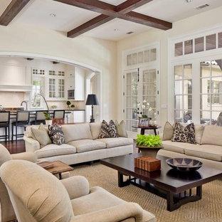 Imagen de sala de estar abierta, clásica renovada, grande, sin televisor, con paredes beige, suelo de madera oscura, chimenea tradicional y suelo marrón
