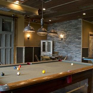 Foto de sala de juegos en casa industrial con paredes beige y suelo de cemento