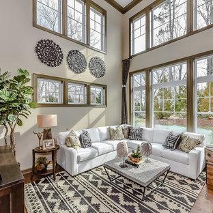 Imagen de sala de estar abierta, tradicional renovada, pequeña, con paredes beige, suelo de madera clara y televisor colgado en la pared