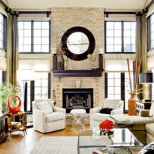 シカゴの中サイズのコンテンポラリースタイルのおしゃれなオープンリビング (ベージュの壁、淡色無垢フローリング、レンガの暖炉まわり、標準型暖炉) の写真