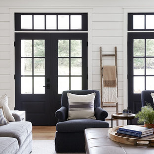 Inspiration for a large farmhouse open plan family and games room in Philadelphia with white walls, light hardwood flooring, a standard fireplace, a brick fireplace surround and a wall mounted tv.