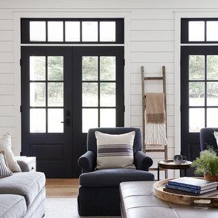 Ejemplo de sala de estar abierta, de estilo de casa de campo, grande, con paredes blancas, suelo de madera clara, chimenea tradicional, marco de chimenea de ladrillo y televisor colgado en la pared