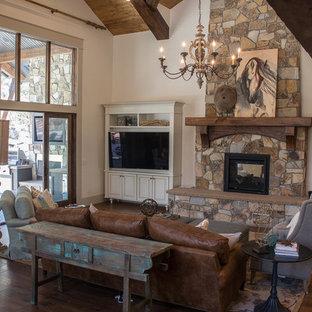 Idées déco pour une salle de séjour avec une bibliothèque ou un coin lecture craftsman de taille moyenne et ouverte avec un mur beige, un sol en bois foncé, une cheminée double-face, un manteau de cheminée en pierre et télé d'angle.