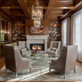 Inspiration for a timeless medium tone wood floor family room library remodel in Los Angeles with a standard fireplace and a wall-mounted tv