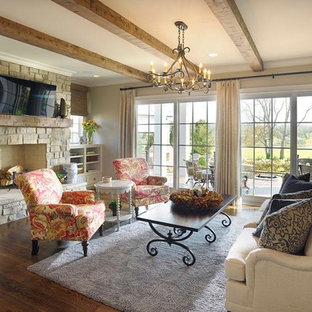 Inspiration for a large farmhouse open concept medium tone wood floor family room remodel in Nashville with beige walls, a standard fireplace, a stone fireplace and a wall-mounted tv
