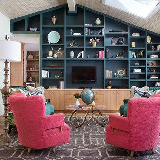 オースティンのトランジショナルスタイルのおしゃれなファミリールーム (ライブラリー、青い壁、淡色無垢フローリング、埋込式メディアウォール、ベージュの床) の写真