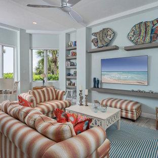 マイアミの大きいビーチスタイルのおしゃれなファミリールーム (青い壁、磁器タイルの床、壁掛け型テレビ、ベージュの床) の写真
