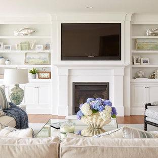Foto di un grande soggiorno chic aperto con pareti beige, pavimento in legno massello medio, camino classico, cornice del camino in legno, TV a parete e pavimento marrone