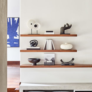 Aménagement d'une grande salle de séjour contemporaine fermée avec un mur blanc, un sol en bois foncé, une cheminée standard, un manteau de cheminée en béton, un téléviseur fixé au mur et un sol marron.