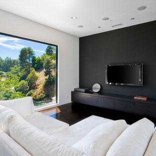 ロサンゼルスのコンテンポラリースタイルのおしゃれなファミリールーム (黒い壁、濃色無垢フローリング、壁掛け型テレビ、茶色い床) の写真