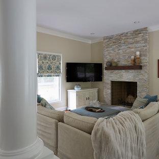 Imagen de sala de estar abierta, tradicional renovada, pequeña, con paredes beige, suelo de madera en tonos medios, chimenea tradicional, marco de chimenea de piedra, televisor colgado en la pared y suelo marrón