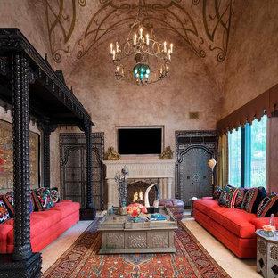 Exemple d'une salle de séjour méditerranéenne avec un mur beige, une cheminée standard et un téléviseur fixé au mur.