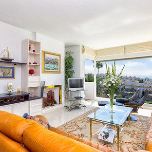 マラガの広い地中海スタイルのおしゃれな独立型ファミリールーム (白い壁、トラバーチンの床、標準型暖炉、金属の暖炉まわり、据え置き型テレビ) の写真