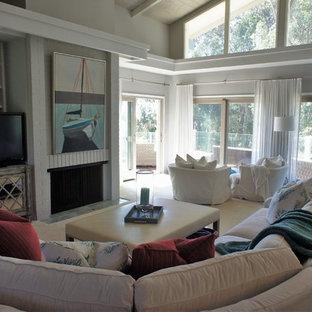 サンフランシスコの中サイズのビーチスタイルのおしゃれなファミリールーム (グレーの壁、カーペット敷き、標準型暖炉、レンガの暖炉まわり、据え置き型テレビ、ベージュの床) の写真