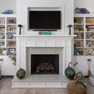 チャールストンの小さいビーチスタイルのおしゃれなファミリールーム (白い壁、淡色無垢フローリング、標準型暖炉、コンクリートの暖炉まわり、ベージュの床) の写真