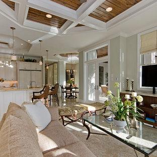 Ispirazione per un ampio soggiorno costiero aperto con libreria, pareti verdi, pavimento in marmo, nessun camino e TV nascosta