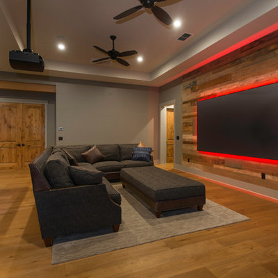Mountain style open concept medium tone wood floor and brown floor family room photo in Austin with gray walls
