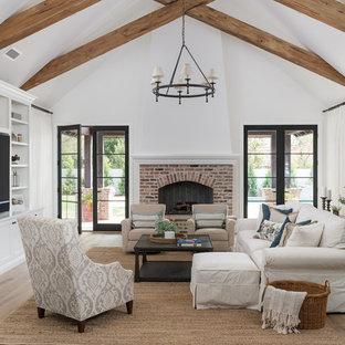 Imagen de sala de estar abierta, campestre, grande, con paredes blancas, suelo de madera en tonos medios, chimenea tradicional, marco de chimenea de ladrillo, pared multimedia y suelo beige
