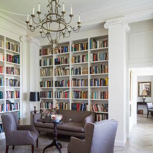 Imagen de sala de estar con biblioteca clásica, grande, sin chimenea y televisor, con paredes blancas y suelo de madera clara