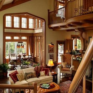 Immagine di un grande soggiorno american style aperto con pareti beige, parquet scuro, camino bifacciale, cornice del camino piastrellata e TV nascosta