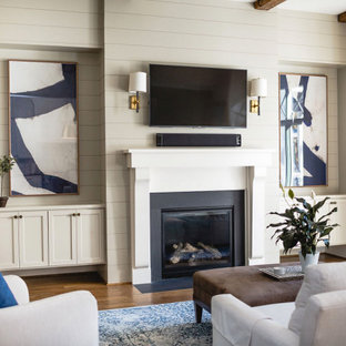 Offenes Klassisches Wohnzimmer mit beiger Wandfarbe, dunklem Holzboden, Kamin, Wand-TV, freigelegten Dachbalken und Holzdielenwänden in Raleigh