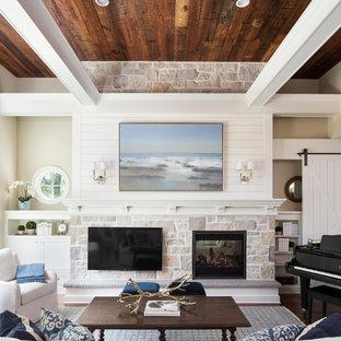 ミネアポリスの中サイズのビーチスタイルのおしゃれなファミリールーム (両方向型暖炉、石材の暖炉まわり、壁掛け型テレビ、白い壁、濃色無垢フローリング) の写真