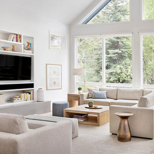Example of a danish open concept light wood floor family room library design with white walls, no fireplace and a media wall