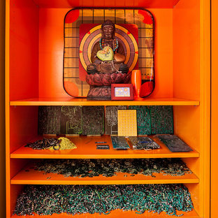 Exemple d'une petite salle de séjour éclectique avec salle de jeu, un téléviseur dissimulé et un mur orange.