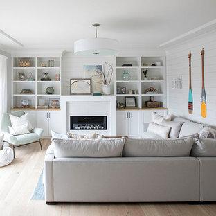 エドモントンの中サイズのビーチスタイルのおしゃれなファミリールーム (白い壁、淡色無垢フローリング、横長型暖炉、タイルの暖炉まわり、テレビなし、ベージュの床) の写真