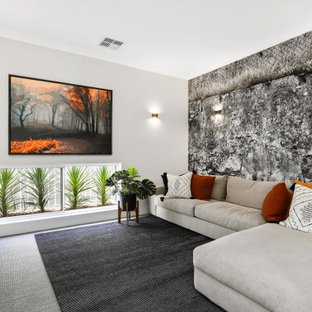 Photo of a mid-sized contemporary enclosed family room in Perth with white walls, carpet, a wall-mounted tv and grey floor.