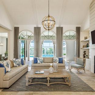 Ejemplo de sala de estar abierta, clásica, con paredes beige, chimenea tradicional y televisor colgado en la pared