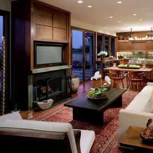 Idée de décoration pour une salle de séjour asiatique ouverte avec un sol en bois brun, une cheminée standard et un téléviseur dissimulé.