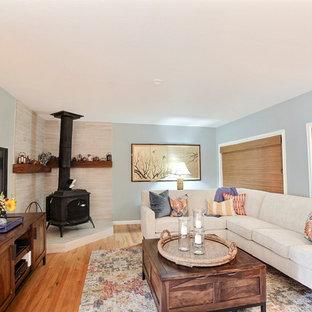 サンフランシスコの中サイズのビーチスタイルのおしゃれな独立型ファミリールーム (緑の壁、無垢フローリング、コーナー設置型暖炉、タイルの暖炉まわり、壁掛け型テレビ、茶色い床) の写真
