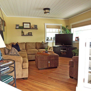Klassisches Wohnzimmer mit beiger Wandfarbe, braunem Holzboden und freistehendem TV in Los Angeles