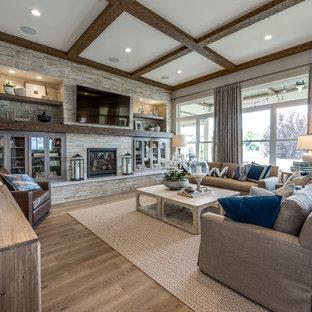 Idéer för stora vintage allrum med öppen planlösning, med grå väggar, ljust trägolv, en standard öppen spis, en spiselkrans i sten, en väggmonterad TV och brunt golv