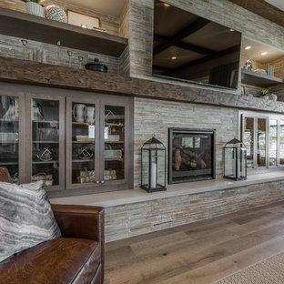ソルトレイクシティの大きいトラディショナルスタイルのおしゃれなファミリールーム (グレーの壁、淡色無垢フローリング、標準型暖炉、石材の暖炉まわり、壁掛け型テレビ、茶色い床) の写真