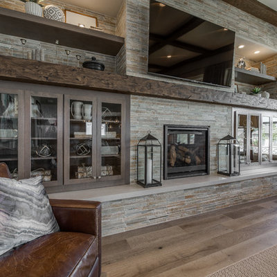 Family room - large traditional open concept light wood floor and brown floor family room idea in Salt Lake City with gray walls, a standard fireplace, a stone fireplace and a wall-mounted tv