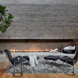 デンバーのコンテンポラリースタイルのおしゃれなファミリールーム (グレーの壁、無垢フローリング、横長型暖炉、レンガの暖炉まわり、茶色い床) の写真