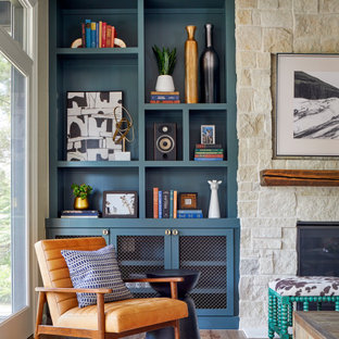 Inspiration for a large eclectic open concept medium tone wood floor and brown floor family room remodel in Denver with gray walls, a standard fireplace, a stone fireplace and a wall-mounted tv