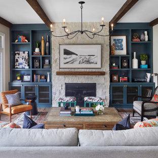 デンバーの広いトランジショナルスタイルのおしゃれなオープンリビング (グレーの壁、無垢フローリング、標準型暖炉、石材の暖炉まわり、壁掛け型テレビ、茶色い床) の写真