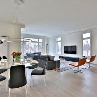 Modelo de sala de estar abierta, minimalista, extra grande, con paredes blancas, suelo de madera clara, chimenea lineal y televisor colgado en la pared